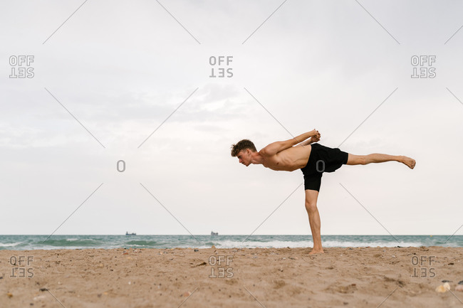 Full body side view of focused slim young male with naked torso standing in Warrior III pose with arms behind back while practicing yoga on sandy beach in cloudy summer day