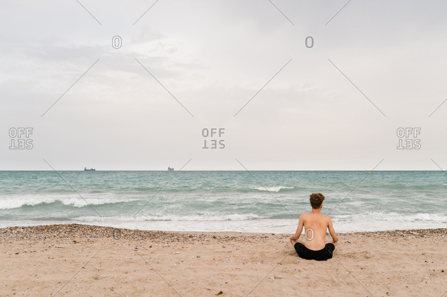 Full body back view of unrecognizable serene young shirtless male sitting in Lotus pose on sand while practicing yoga meditation near sea