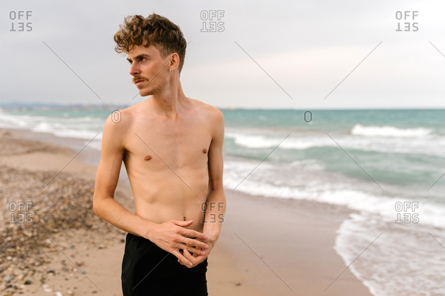 Serious slim young shirtless curly haired male with mustache and piercing looking away while standing against waving sea on beach
