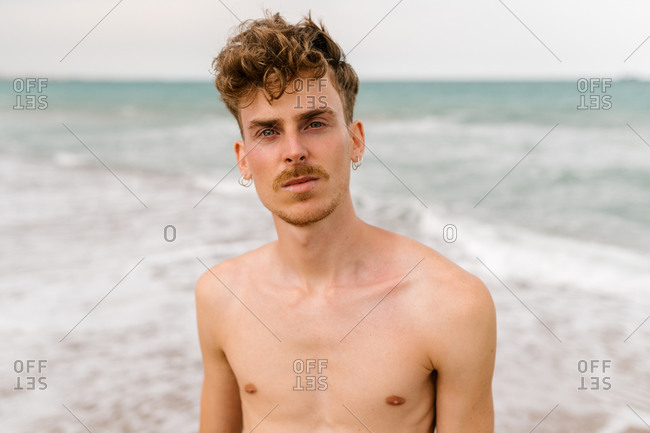 Serious young shirtless curly haired male with mustache and piercing looking at camera while standing against waving sea on beach