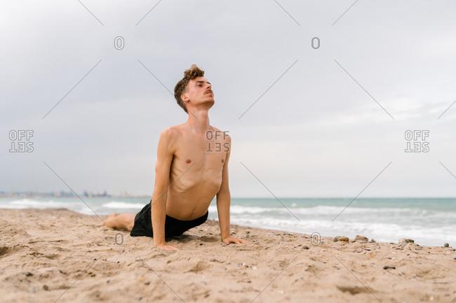 Full body of slim shirtless man doing cobra pose during yoga practice on sandy beach near sea