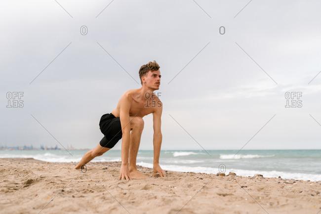 Full body of slim shirtless man doing high lunge pose during yoga practice on sandy beach near sea