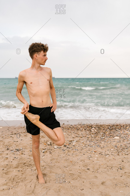 Full body of young slim male with naked torso keeping leg in Standing Half Lotus position and looking away while practicing yoga on sandy sea coast