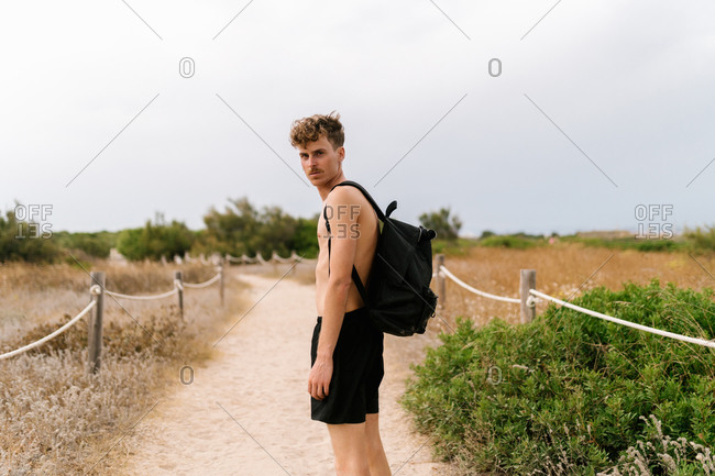 Side view of serious active shirtless male in black shorts with backpack standing on fenced path amidst field and looking at camera in cloudy summer day in countryside
