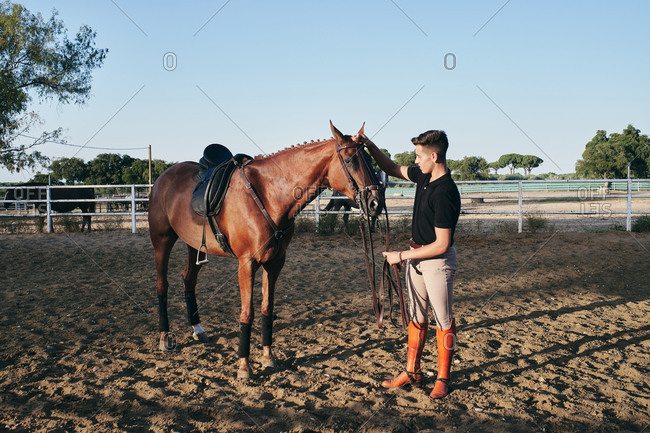 Male jockey in boots getting ready to ride a chestnut horse on sand arena on ranch in summer