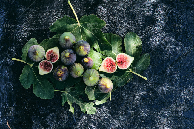 From above closeup of fresh ripe figs arranged placed on top of green leaves placed on black slate board