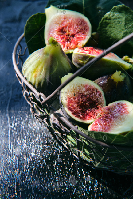 From above closeup of fresh ripe figs arranged in basket with green leaves placed on black slate board