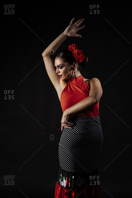 Seductive young Hispanic female in traditional red costume performing sensual Flamenco dance and looking down
