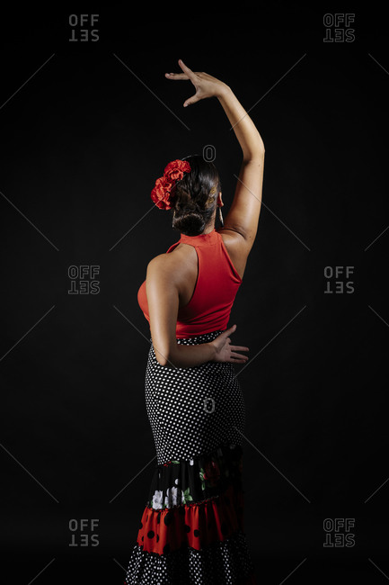 Seductive young Hispanic female in traditional red costume performing sensual Flamenco dance