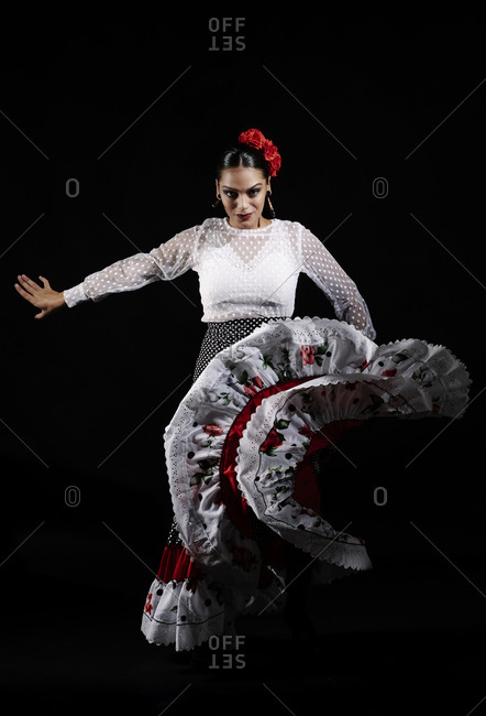 Full body elegant young Hispanic woman in traditional outfit dancing Flamenco dance against black background