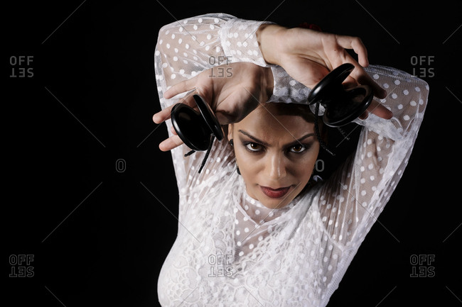 From above of young Hispanic woman in white blouse performing traditional Flamenco dance with castanets in raised arms