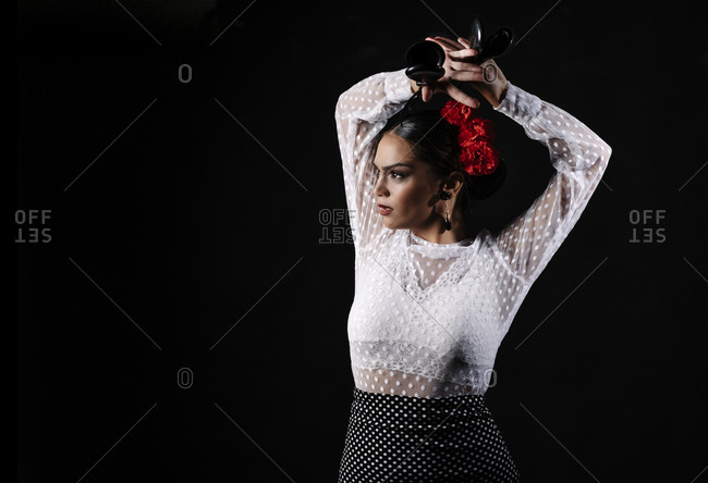 Young Hispanic woman in white blouse performing traditional Flamenco dance with castanets in raised arms