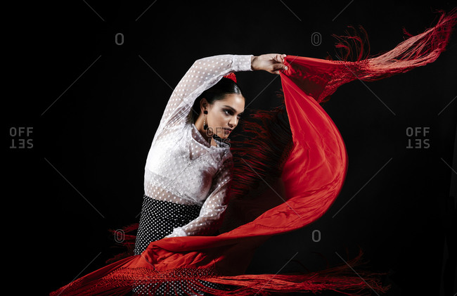Seductive young Hispanic female in traditional red costume performing sensual Flamenco dance and looking away