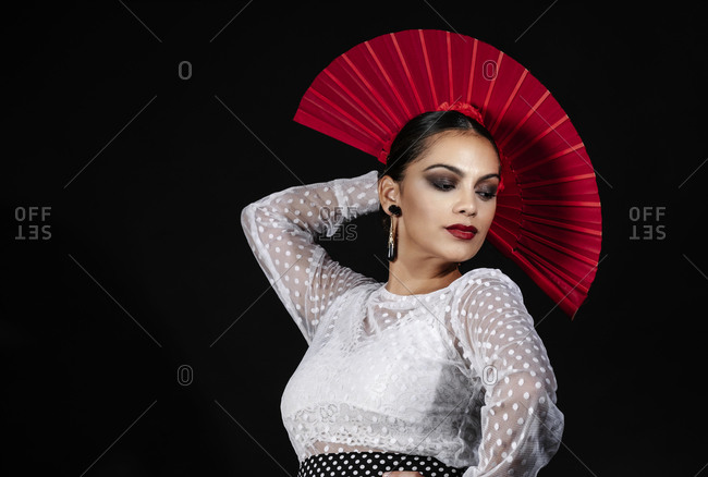Full body young Hispanic female dancer in colorful costume with red fan in hand performing expressive Flamenco dance on black background