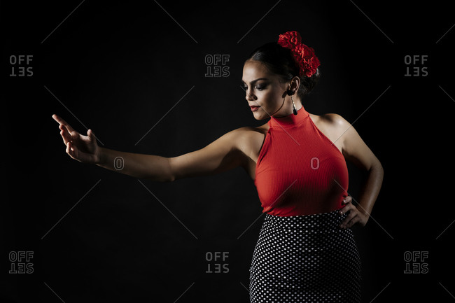 Graceful young Hispanic female in red tight top and skirt dancing traditional Flamenco dance against black background
