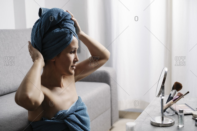 Side view of young bare shouldered female with bath towel on head sitting near table with cosmetics and mirror and preparing for beauty procedure at home