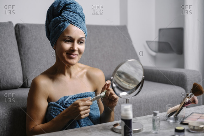 Smiling young female wrapped in bath towels holding tube with cosmetic cream while sitting at table with mirror and applying makeup after taking shower