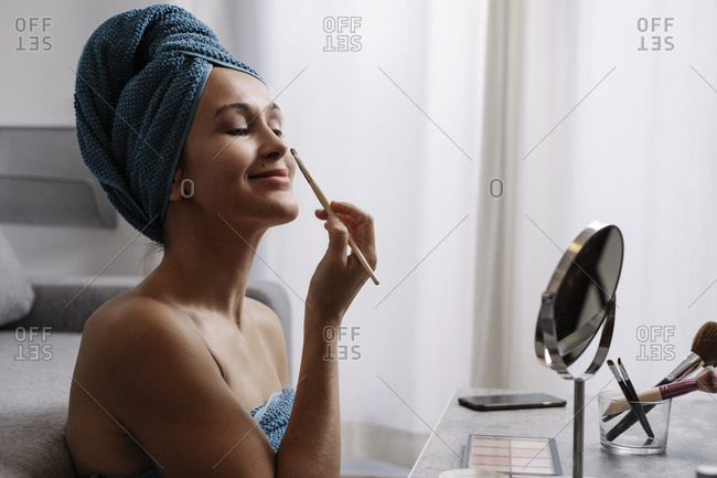 Content young bare shouldered female with towel on head applying eye shadow on eyebrows during makeup procedure after shower at home