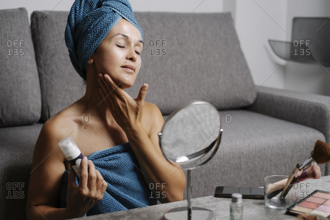 Charming young female with bare shoulders and towel on head smearing facial skincare cream on face during makeup procedure at home