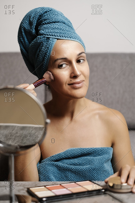 Positive young female wrapped in towels applying powder with brush while doing makeup after shower at home