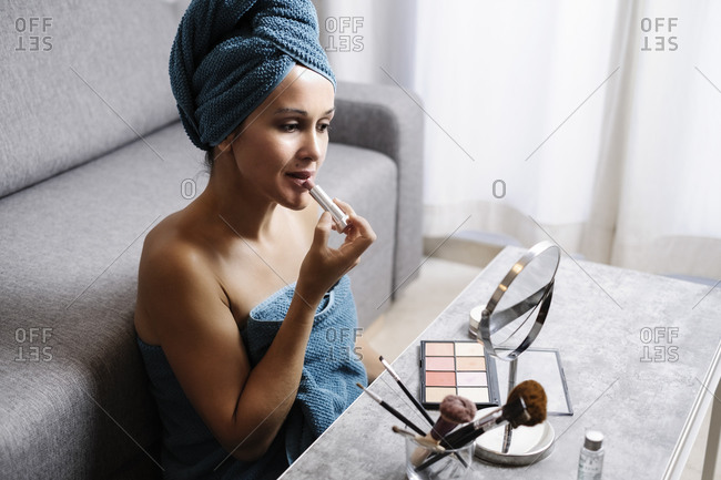 Side view of female applying natural colored lipstick during morning beauty routine