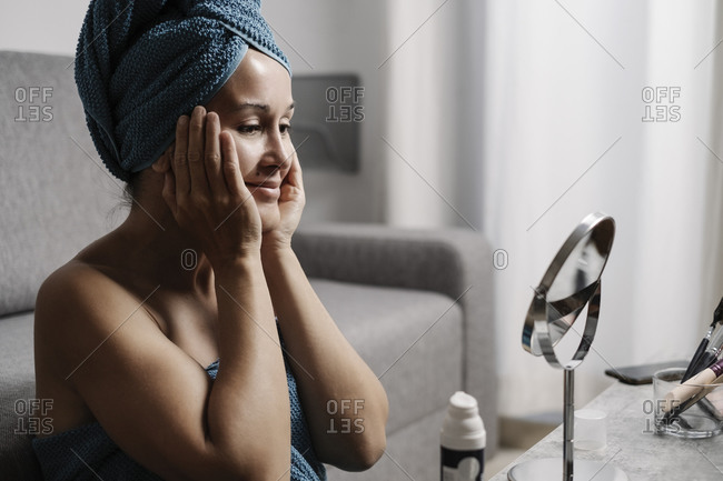 Side view of charming young female with bare shoulders and towel on head smearing facial skincare cream on face during makeup procedure at home