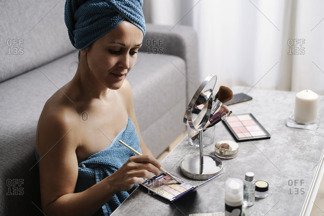 Side view of female taking eye shadow from palette with makeup brush during beauty procedure at home
