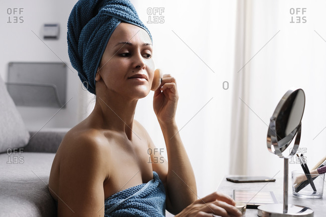 Positive young female wrapped in towels applying powder with powder puff while doing makeup after shower at home