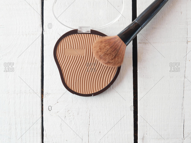 From above compact cosmetic face powder in open box and makeup brush placed on wooden surface