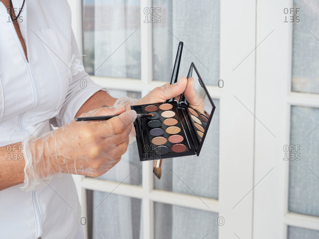 Side view of crop female cosmetician in protective gloves holding makeup brushes and eye shadow palette with mirror while working in modern salon