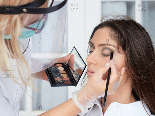 Focused woman in protective mask and gloves applying eyeshadow makeup to female model in studio