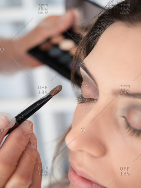 Cropped unrecognizable focused woman in protective mask and gloves applying eyeshadow makeup to female model in studio