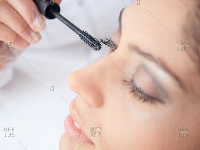 Cropped faceless visagiste in gloves applying mascara on eyelashes of sensual brunette with makeup
