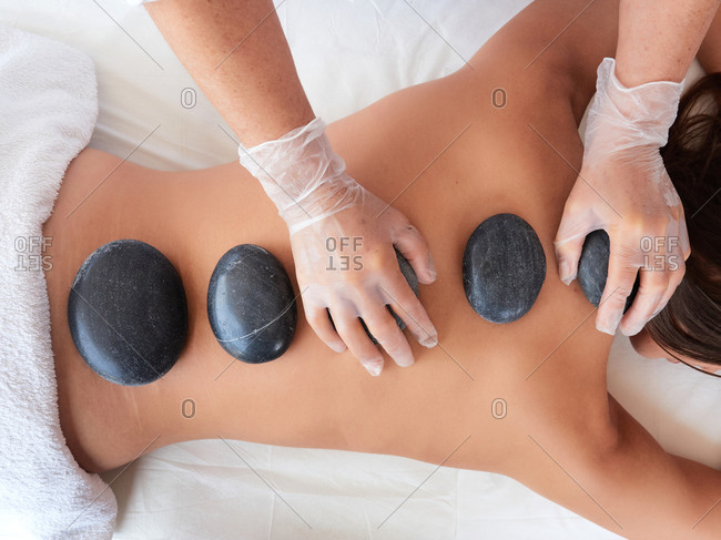 Top view of cropped unrecognizable adult artist in virus protection placing hot stones on spine of topless brunette on salon terrace