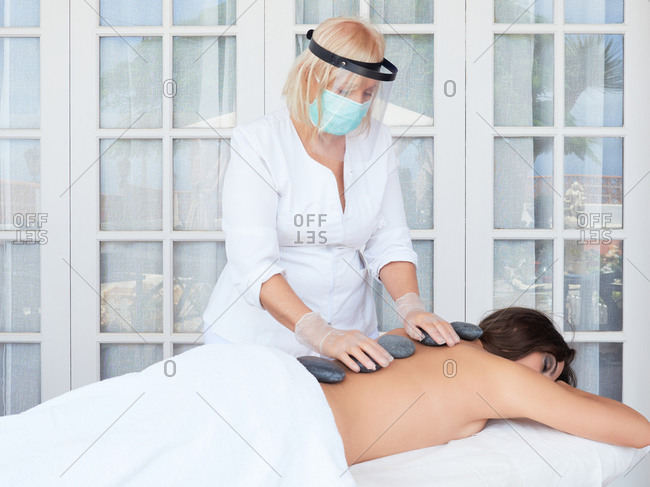 Adult artist in virus protection placing hot stones on spine of topless brunette on salon terrace