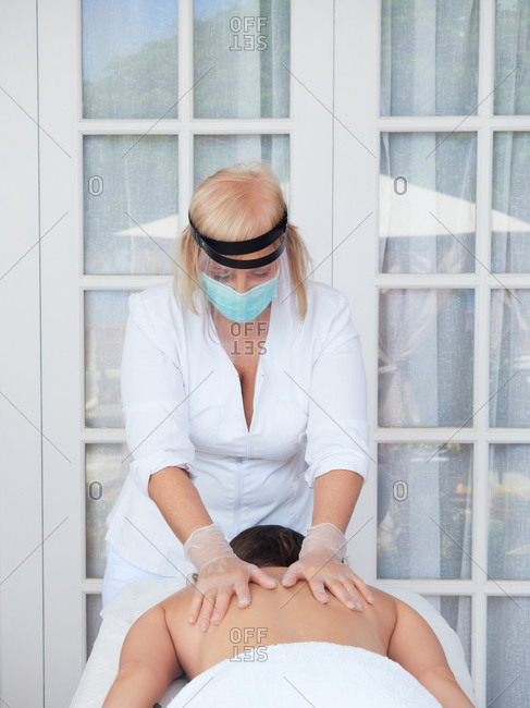 Adult female masseur in face mask with shield and gloves rubbing back of woman lying on table