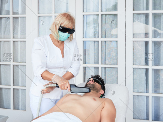 Professional woman in dark glasses and mask doing laser hair removal on chest to bearded man in salon