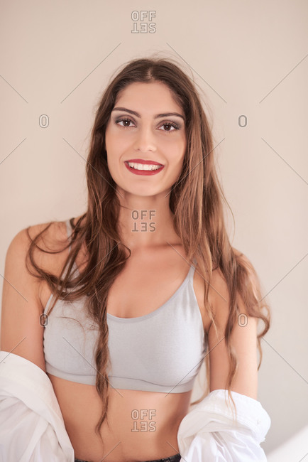 Skinny brunette with long hair wearing simple top with shirt and sensual makeup with red lips smiling at camera