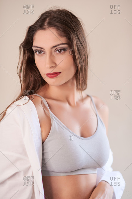 Skinny brunette with long hair wearing simple top with shirt and sensual makeup with red lips looking away