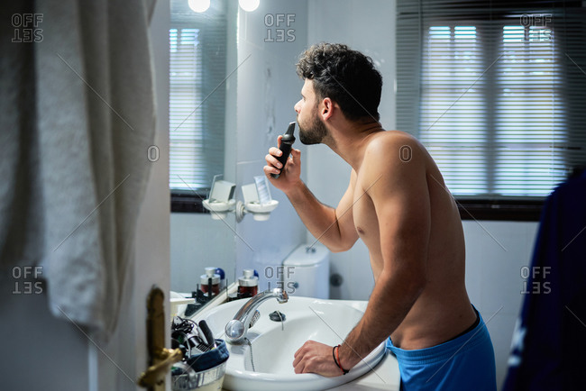 Side view of serious shirtless handsome male using electric shaver for grooming while standing in modern bathroom and looking in mirror