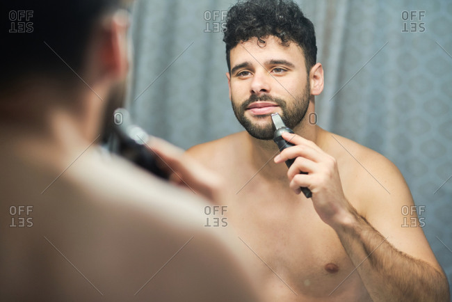 Serious shirtless handsome male using electric shaver for grooming while standing in modern bathroom and looking in mirror
