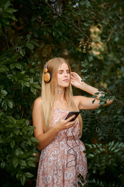 Serene young blond female in summer dress listening to music with smartphone and headphones among green foliage in garden with eyes closed