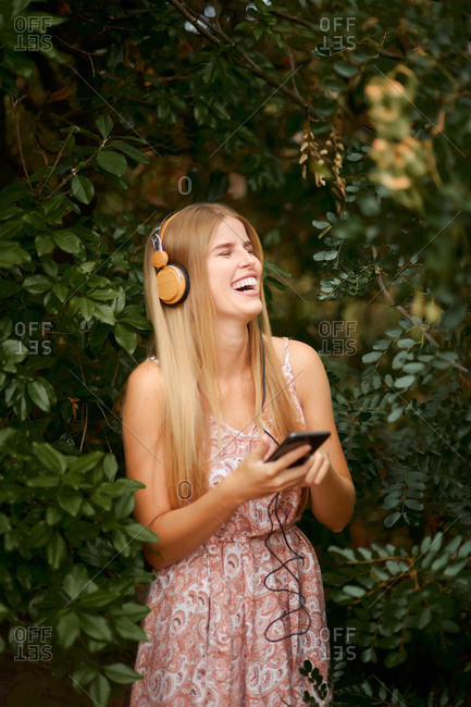 Cheerful young blond female in summer dress laughing happily while listening to music with smartphone and headphones among green foliage in garden