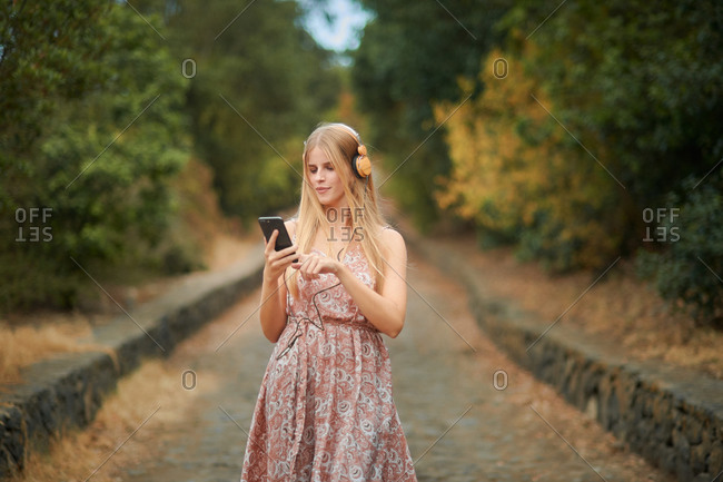 Optimistic young female in stylish summer dress and headphones enjoying music and browsing smartphone while walking on alley in park