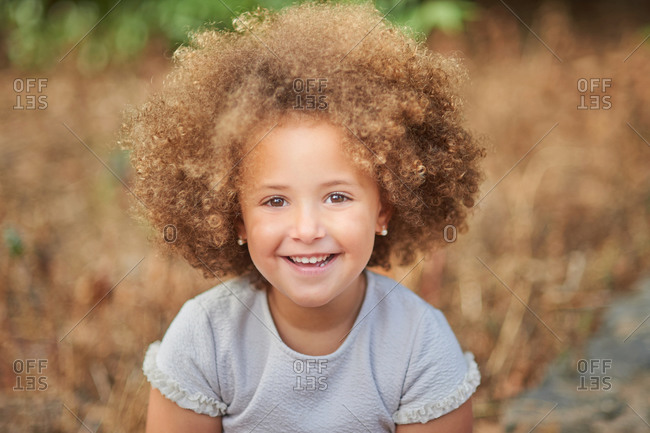 Adorable little girl with blonde Afro hair smiling and looking at camera while spending summer day in nature