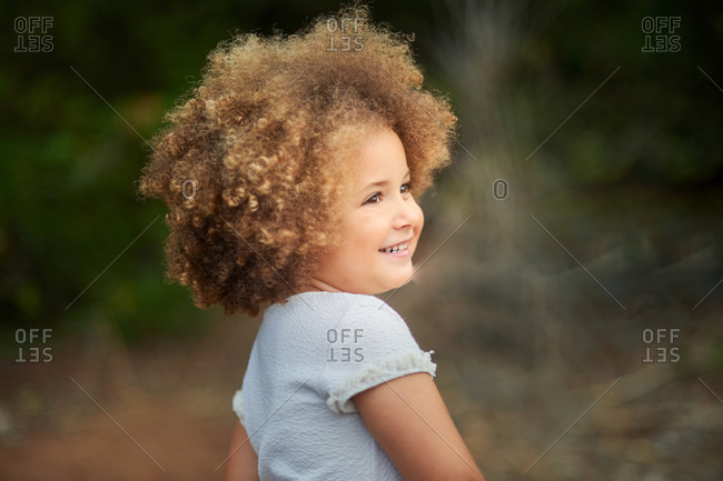 Adorable little girl with blonde Afro hair smiling and looking away while spending summer day in nature