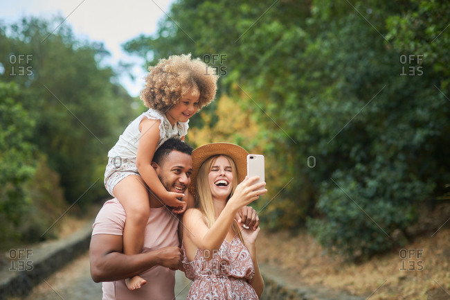 Cheerful multiethnic parents with cute curly hair daughter having fun and taking selfie on smartphone while spending summer day together in park