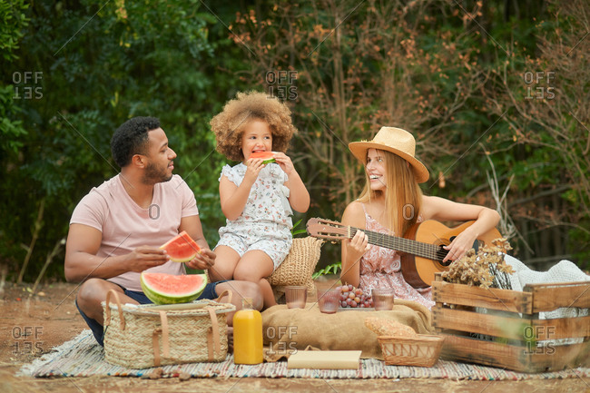 Cheerful young woman playing guitar while husband and little daughter eating watermelon during summer picnic in nature