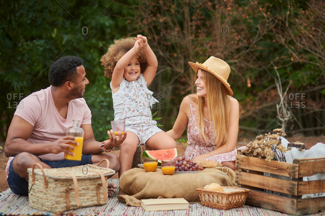 Loving ethnic dad pouring natural orange juice into glass during picnic with wife and little daughter in summer day in nature