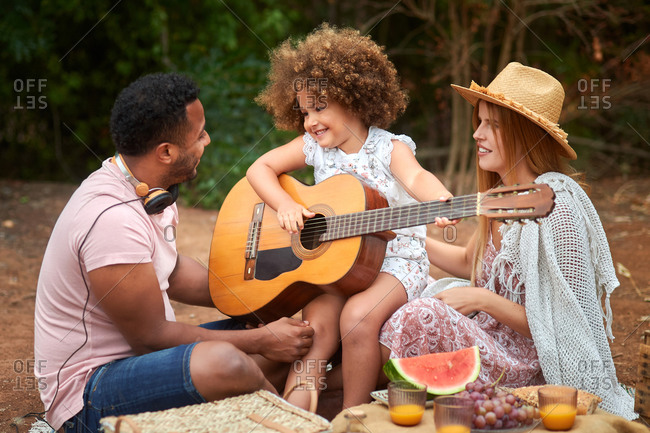 Cute curly haired little girl having fun and playing guitar during picnic with multiracial parents in summer day in nature